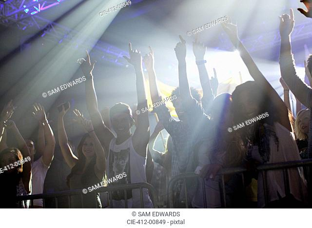 Crowd with arms raised behind railing at concert