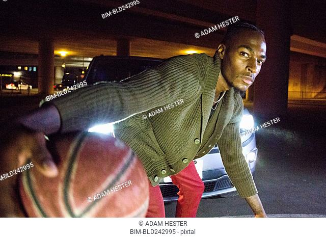 Headlights shining on Black man playing basketball