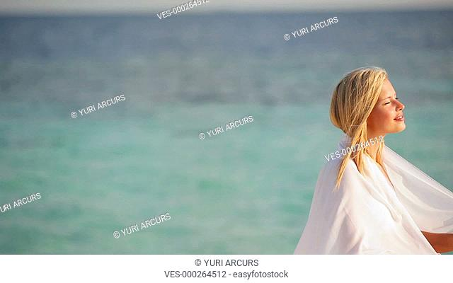 Panning footage of a relaxed woman enjoying a summer breeze with a white sarong at the beach