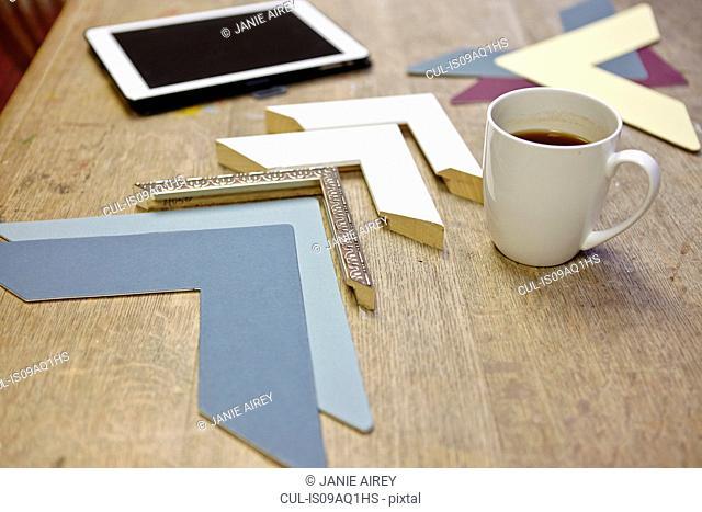 Still life of frames and digital tablet in picture framers workshop