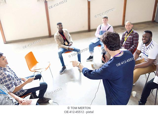 Man with microphone talking to men in group therapy