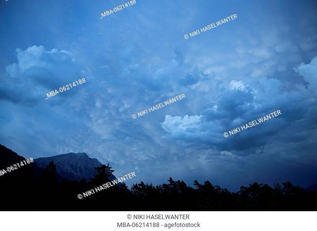 Mammatus clouds with mountain in the background, trees in the foreground