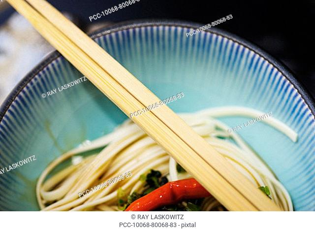 Close-up of a red chili and green garnish on a bed of Japanese soba noodles with chopsticks