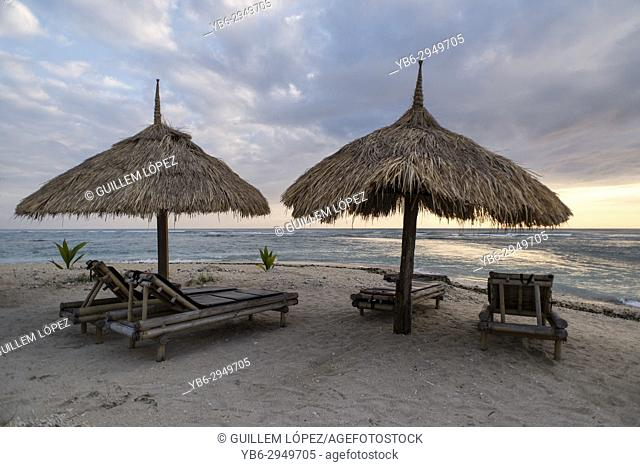 Straw umbrellas and chairs by the shore of a white sand beach, Gili Air, Gili Islands, Indonesia