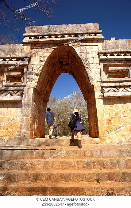 Visitors passing through the Labna Arch in the Labna Archaeological site, Puuc Route, Merida, Yucatan State, Mexico, Central America