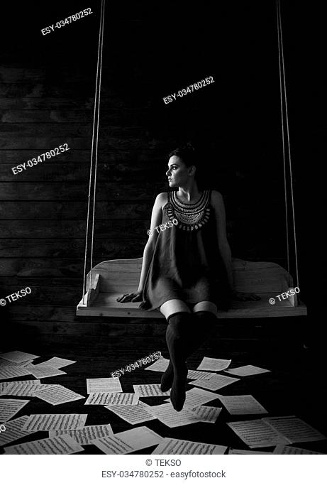 girl posing in a dark room on a swing and holding a violin