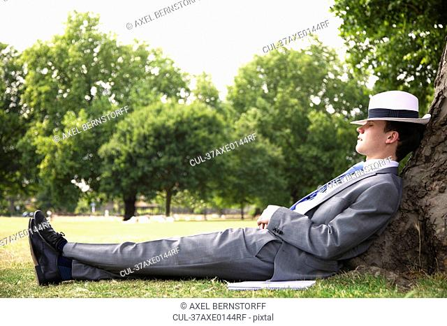 Businessman napping on tree in park