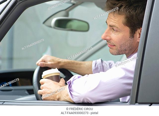 Man driving car with cup of coffee in one hand