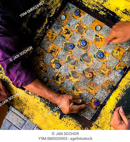 Hands of Salvadoran men are seen moving crown caps while playing checkers on an outdoor checkerboard table in the park in San Salvador, El Salvador