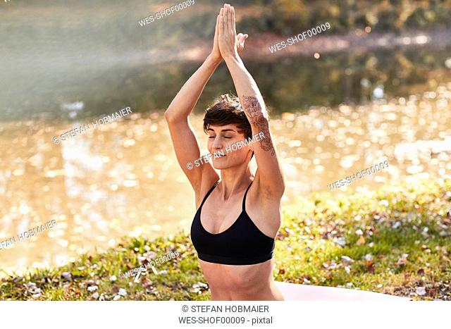 Mid adult woman in forest practicing yoga, meditation