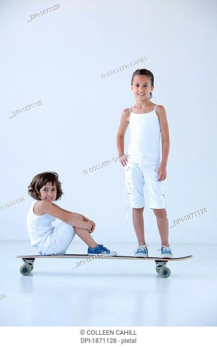 two young girls on a longboard