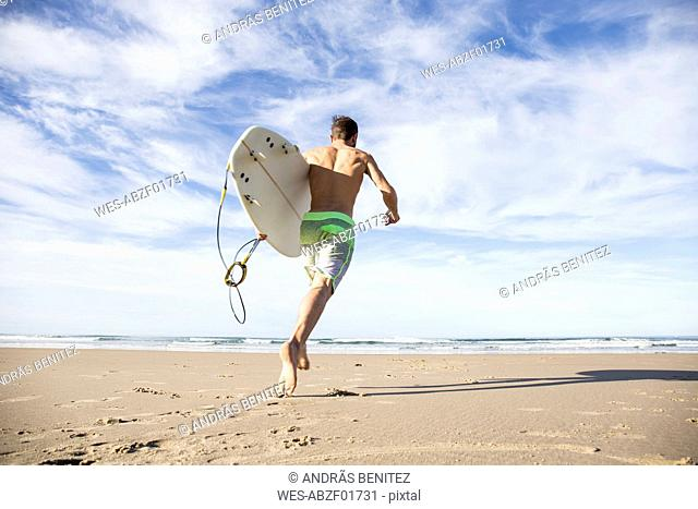 Man carrying surfboard running on the beach