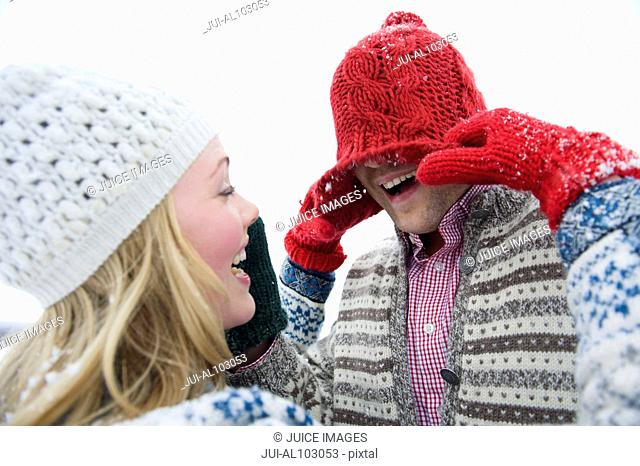 A young couple wearing woolen hats playing in the snow