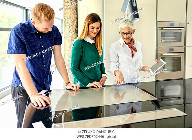 Shop assistant with tablet talking to couple shopping for a new kitchen in showroom
