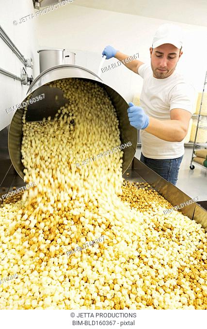 Caucasian worker pouring popcorn in factory
