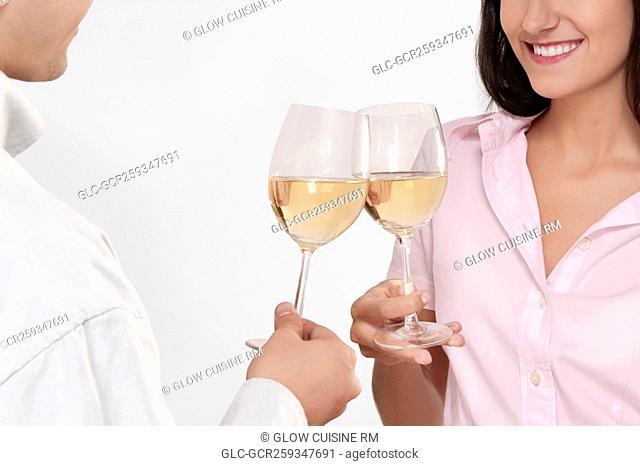 Couple toasting glasses of wine and smiling