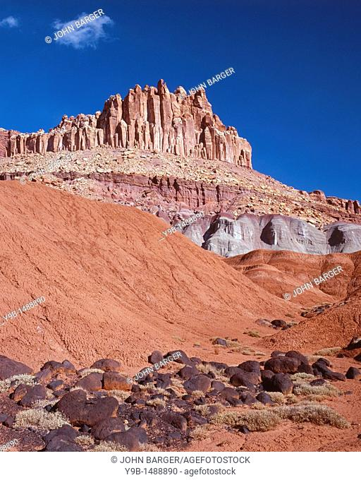 Soft Moenkopi sediments and dark, volcanic boulders beneath The Castle, Capitol Reef National Park, Utah, USA