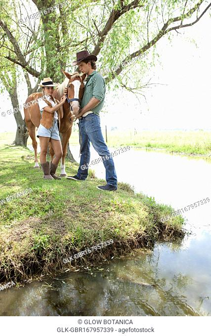 Couple standing with a horse near a pond