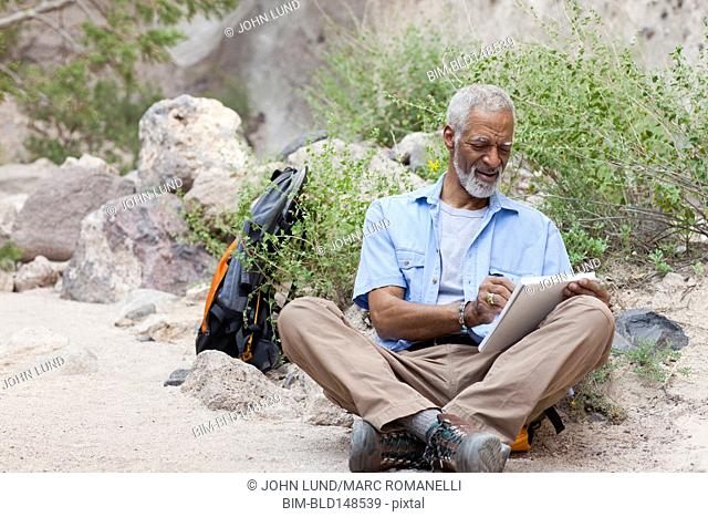 African American man sketching in remote area