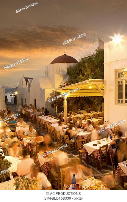 Time lapse view of tourists eating in sidewalk cafe at sunset, Mykonos, Cyclades, Greece