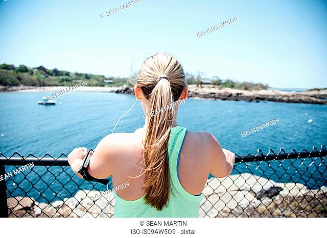 Rear view of woman wearing activity tracker holding wire fence looking at view of ocean