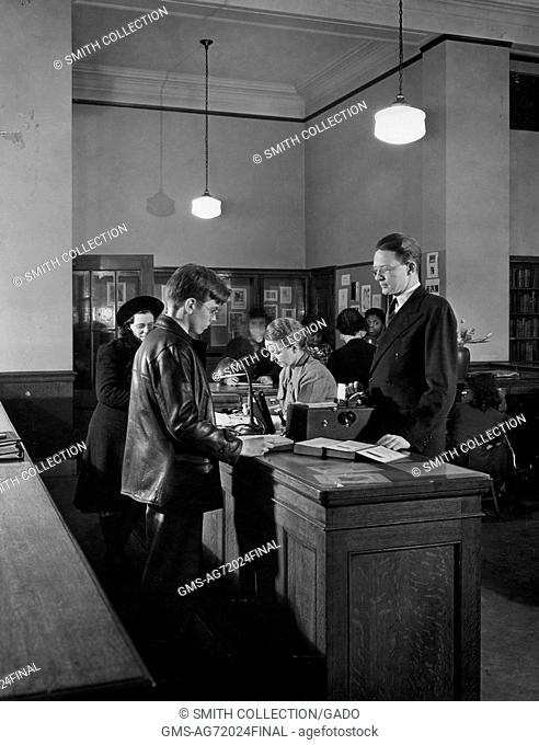 Black and white photograph of librarians at a counter, a man and a woman, helping patrons, a young man wearing a leather jacket and a woman in a hat, 1900