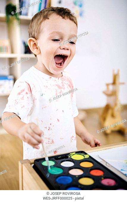 Portrait of laughing little boy painting with watercolours