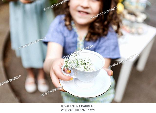 Girl playing tea time with an empty cup and blossoms