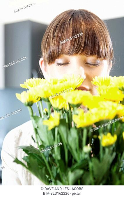 Caucasian woman smelling bouquet of flowers