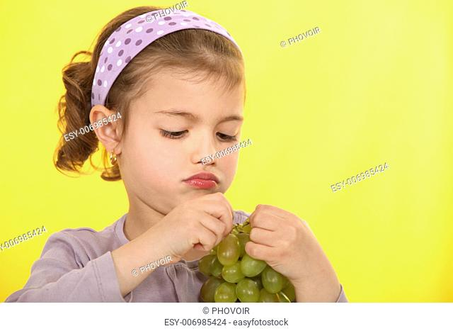 A little girl eating grapes