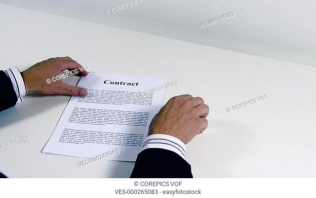 Businessman signing a two page contract in duplicate. The contract text is generic