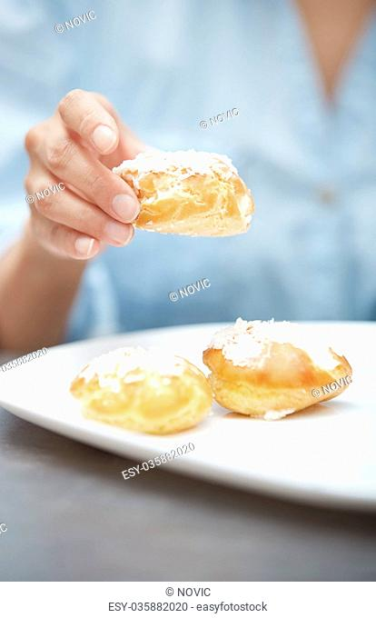 Woman eating eclairs