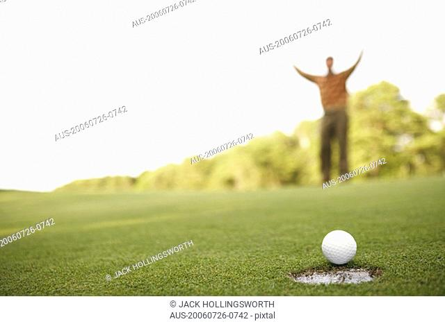 Close-up of a golf ball on the edge of a hole with a man raising his arms in the background