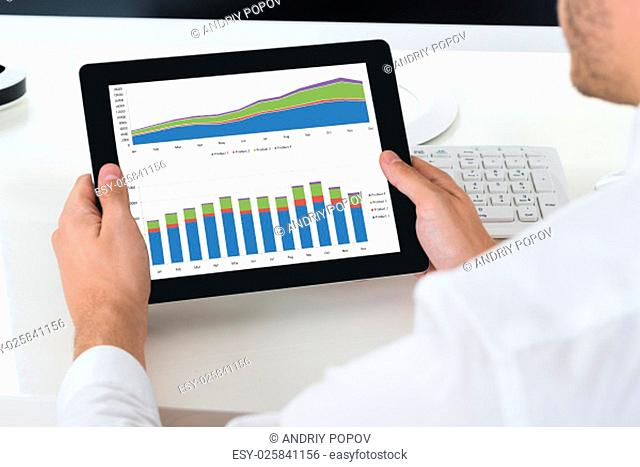 Close-up Of Businessperson Analyzing Graph On Digital Tablet At Desk