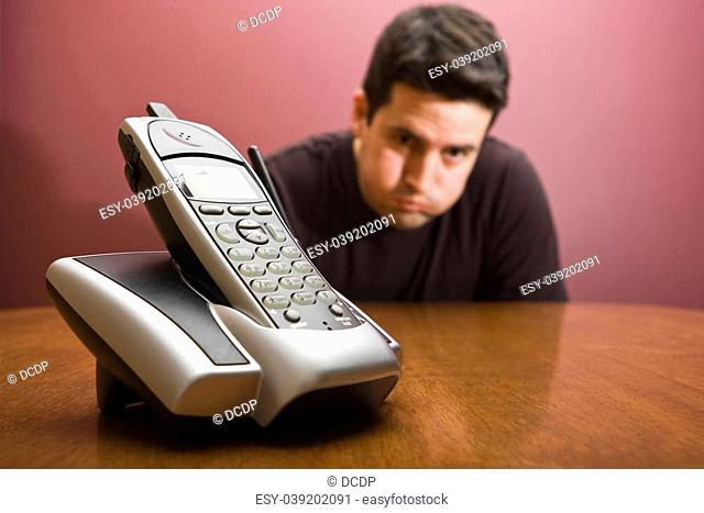A man holds his breathe waiting for the phone