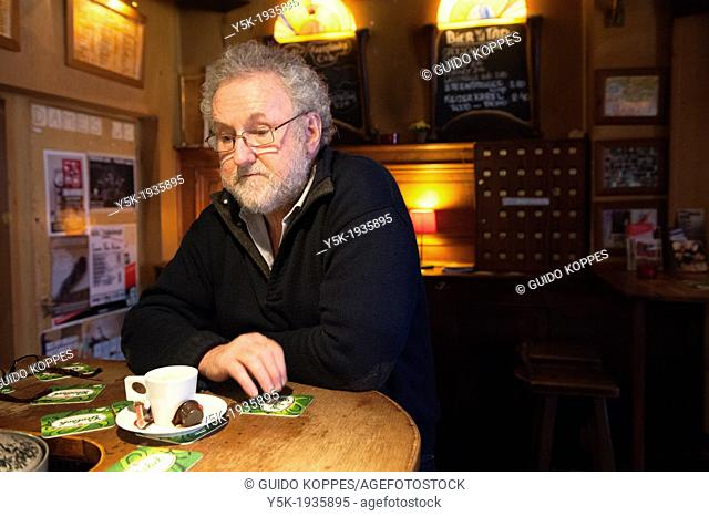 An older man, former owner of the oldest cafe in Tilburg, called Weemoed, at the bar with a cup of coffee