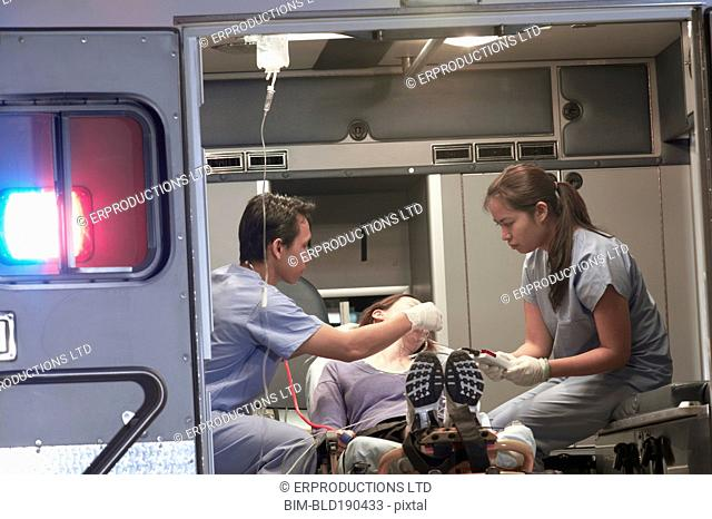 Asian medical professionals with patient in ambulance
