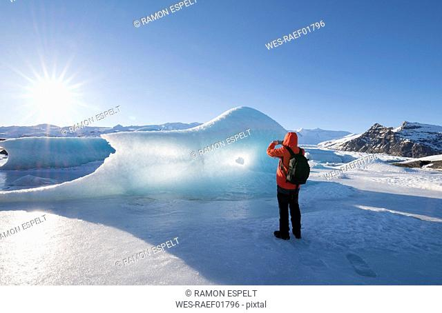 Iceland, tourist taking cell phone picture of glacial ice