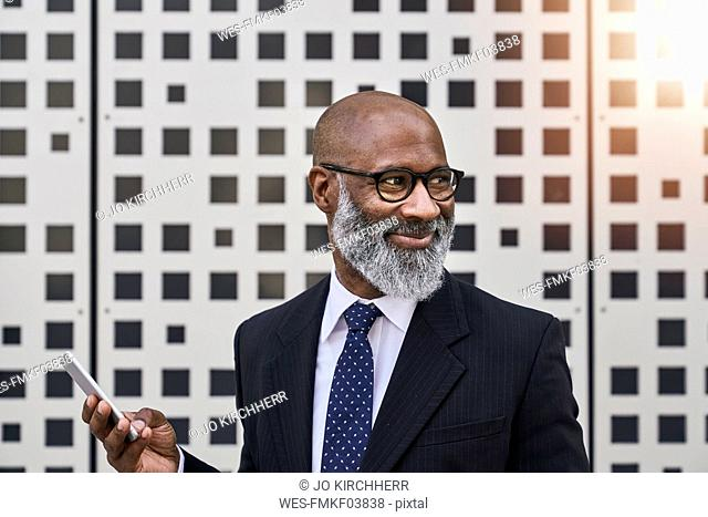 Mature businessman holding smartphone, smiling