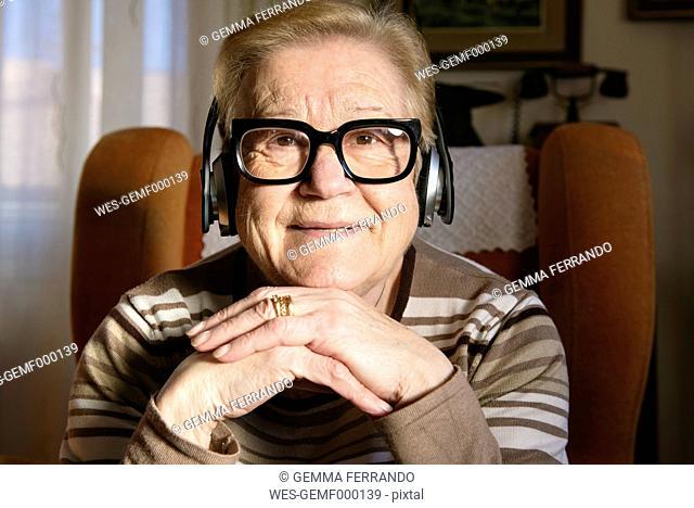 Portrait of elderly lady hearing music with headphones