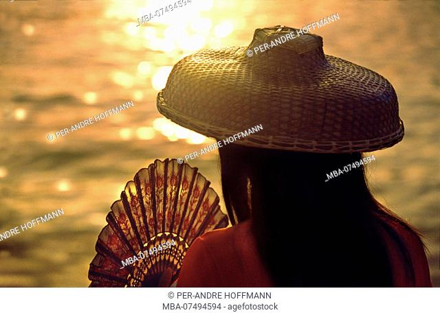 Hakka woman with traditional hat and fan at sunset, New Territories, Hongkong, China