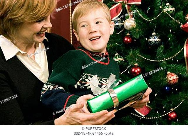 Mature woman opening a present with her grandson
