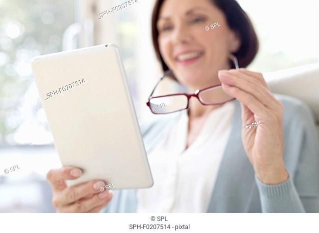Mature woman using digital tablet