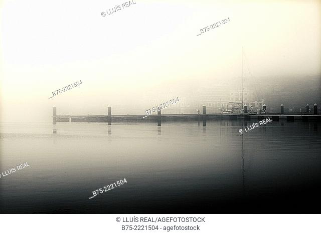 Wharf with yacht moored on a foggy morning in the Port of Mahon, Menorca, Balearic Islands, Mediterranean, Spain