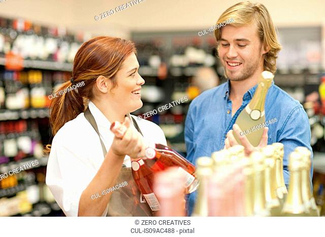 Female shop assistant advising customer on wine