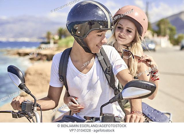 Greece, Crete, Chersonissos, couple driving quad next to coast, girlfriend holding sunglasses of boyfriend, eye protection, caring, playful, teasing