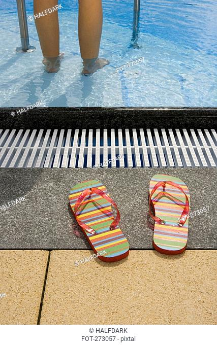 A pair of flip flops next to a swimming pool