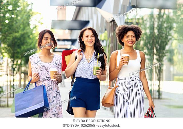 women with shopping bags and drinks in city