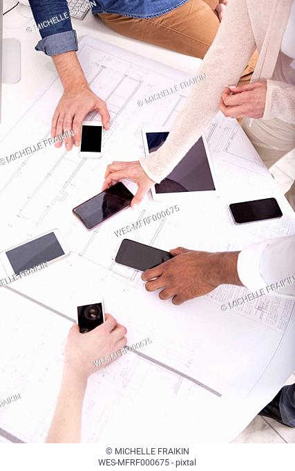 Hands taking smartphones lying on construction plan