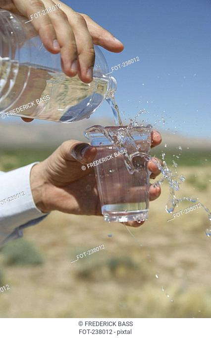 Businessman pouring glass of water in desert